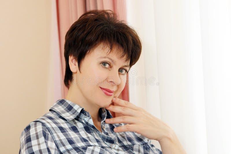 Ritratto di bella donna che si siede accanto ad una finestra fotografia stock