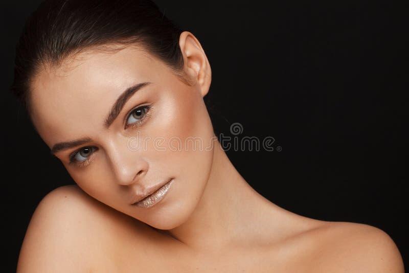 Ritratto di bella donna con capelli raccolti e delle spalle nude su un fondo nero fotografia stock