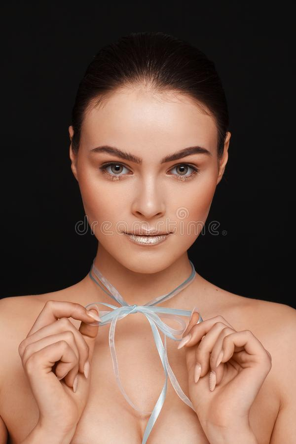 Ritratto di bella donna con capelli raccolti e delle spalle nude su un fondo nero fotografie stock