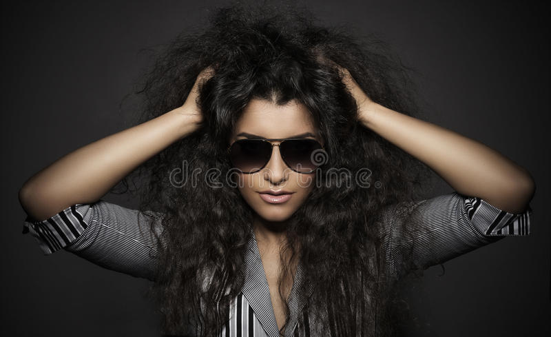 Ritratto di bella donna con i capelli ricci ed i vetri immagini stock