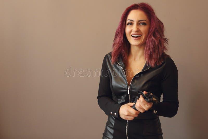 Ritratto di bella donna con la brevi acconciatura e trucco rosa in vestiti di cuoio neri fotografie stock
