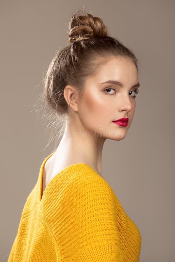 Ritratto di bella donna con trucco su un fondo grigio Maglione arancione fotografie stock