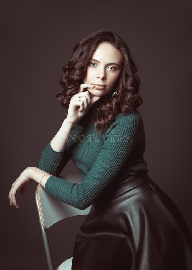 Ritratto di bella donna con trucco, su una sedia, in maglione verde e gonna di cuoio nera che posano sul fondo del cioccolato fon fotografia stock