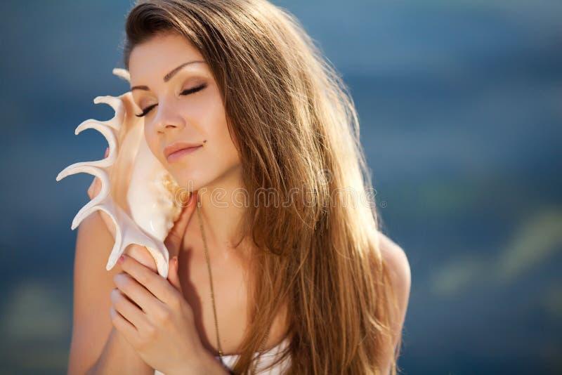 Ritratto di bella donna con una conchiglia all'orecchio fotografie stock libere da diritti