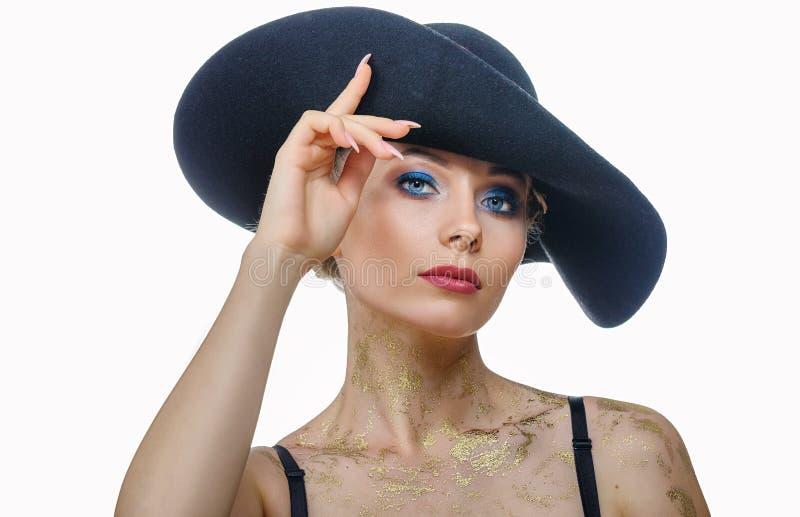 Ritratto di bella donna dentro con trucco in black hat su fondo bianco, isolato fotografia stock