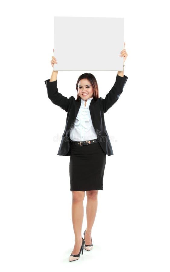 Ritratto di bella donna di affari che rimanda tabellone per le affissioni in bianco fotografia stock libera da diritti