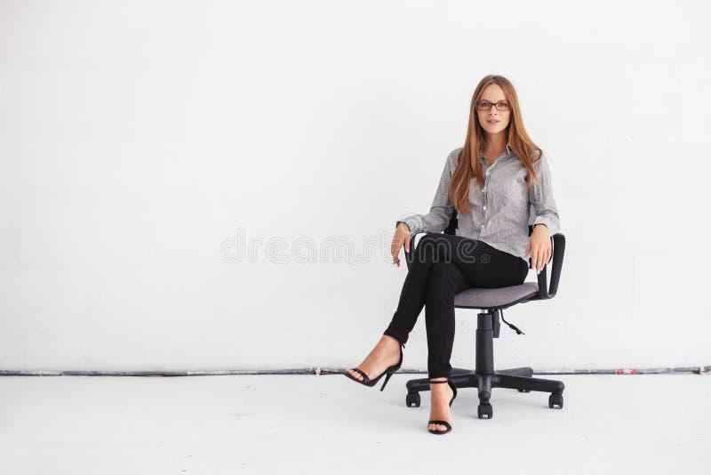 Ritratto di bella donna di affari che si siede sulla sedia contro il wh immagine stock