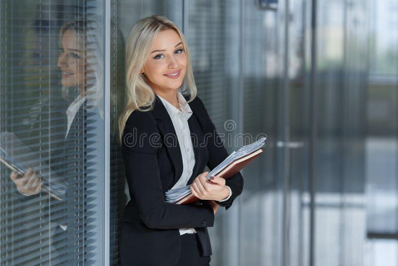 Ritratto di bella donna di affari che sorride e che sta con la cartella nell'ufficio fotografia stock