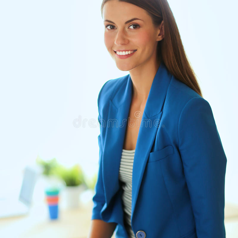 Ritratto di bella donna di affari che sta vicino al suo posto di lavoro fotografia stock