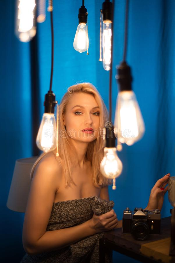 Ritratto di bella donna e delle lampade d'annata Donna che esamina la macchina fotografica fotografie stock