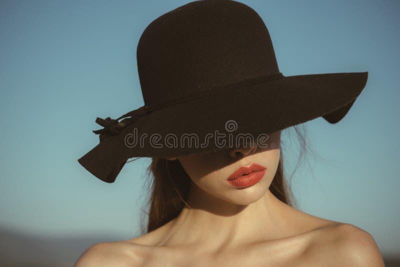 Ritratto di bella donna elegante in un ampio cappello nero sul fondo del cielo blu fotografia stock libera da diritti