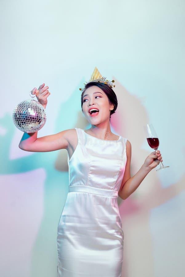 Ritratto di bella donna felice in vestito bianco che ha un partito e che beve champagne mentre stando con la palla della discotec immagine stock