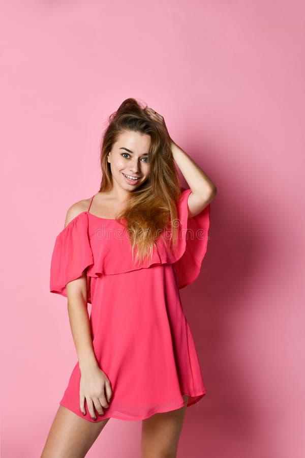 Ritratto di bella donna felice in vestito rosa che posa nello studio fotografia stock libera da diritti