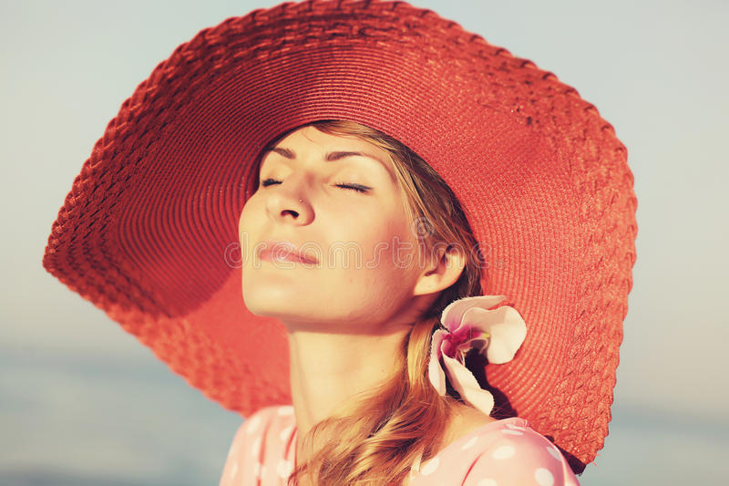 Ritratto di bella donna graziosa in cappello rosa elegante con un ampio bordo Bellezza, concetto di modo immagine stock