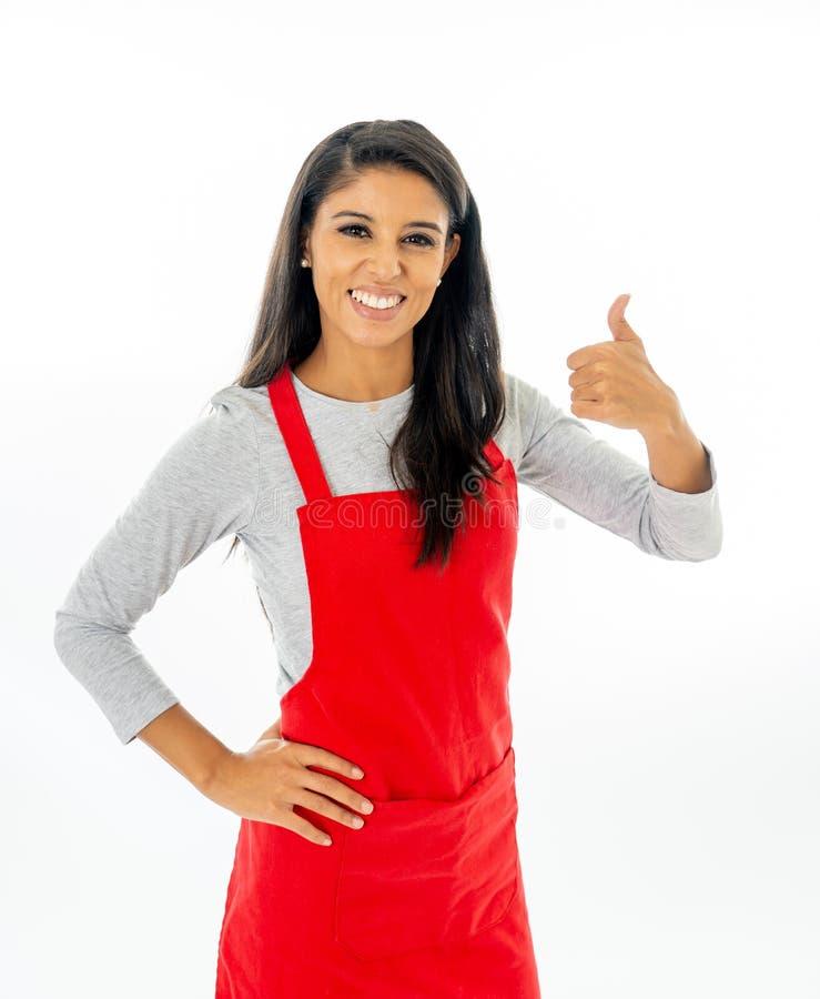 Ritratto di bella donna latina fiera felice che indossa un grembiule rosso che impara cucinare fabbricazione del pollice sul gest fotografie stock libere da diritti