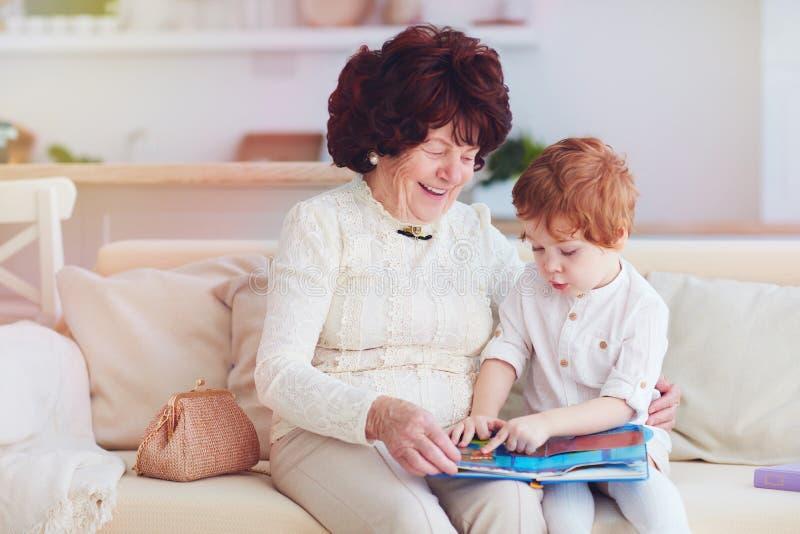 Ritratto di bella donna matura 80 anni con la sua pronipote a casa, leggente insieme libro educativo fotografie stock