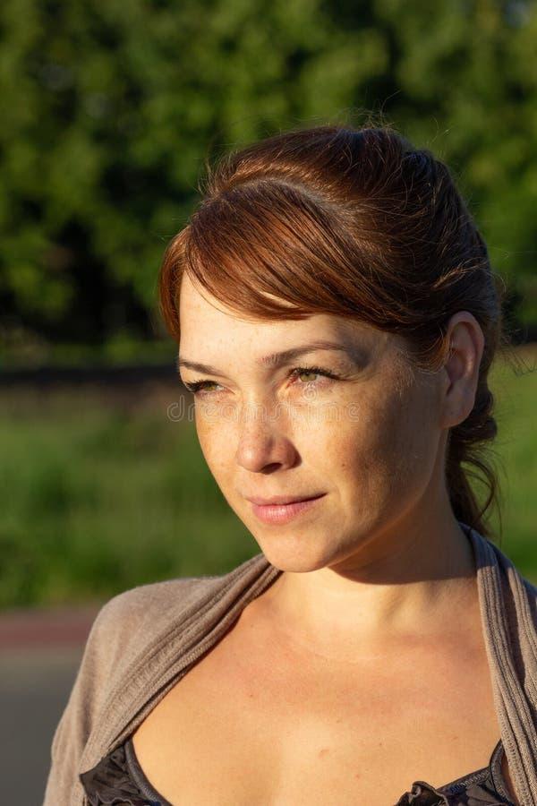 Ritratto di bella donna di mezza età seria con il fronte calmo che guarda da parte nel parco verde di estate fotografia stock