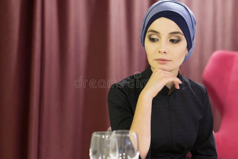 Ritratto di bella donna musulmana ad una tavola in un ristorante fotografia stock