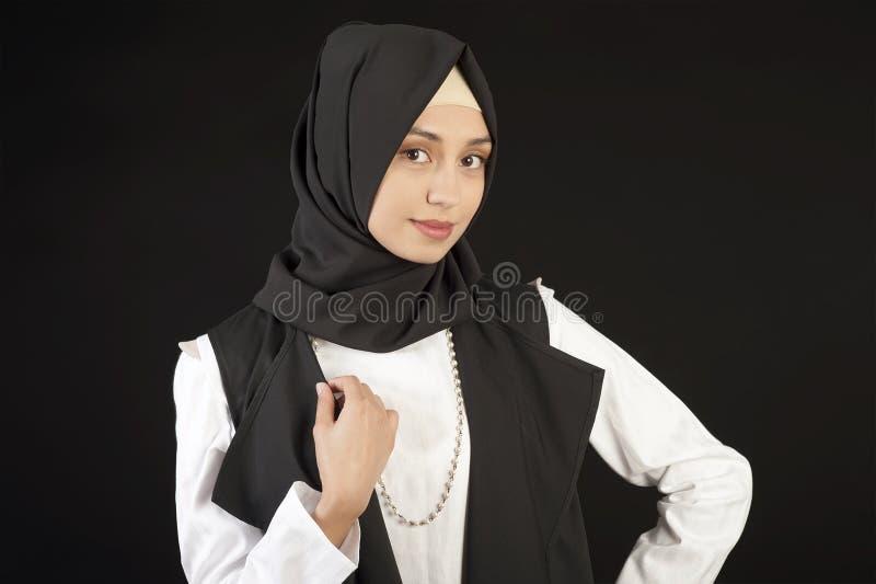 Ritratto di bella donna musulmana in vestiti orientali moderni su un fondo nero isolato fotografia stock