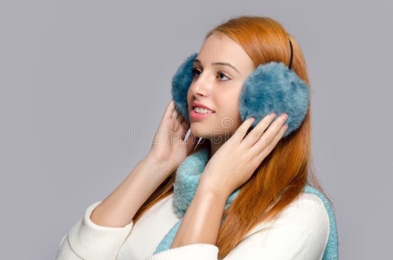 Ritratto di bella donna rossa dei capelli che indossa la cuffia blu fotografia stock