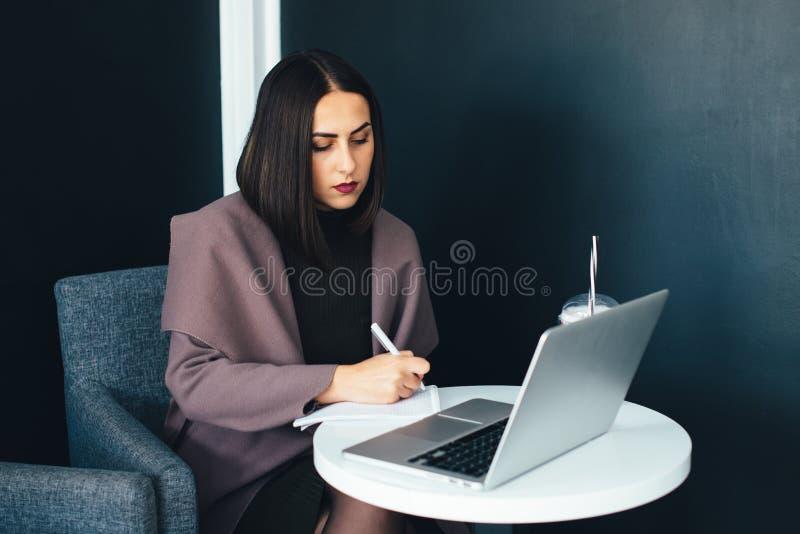 Ritratto di bella donna sorridente che si siede in un caffè con il computer portatile fotografie stock libere da diritti
