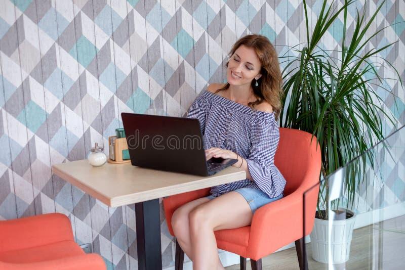 Ritratto di bella donna sorridente che si siede in un caffè con il computer portatile nero fotografie stock