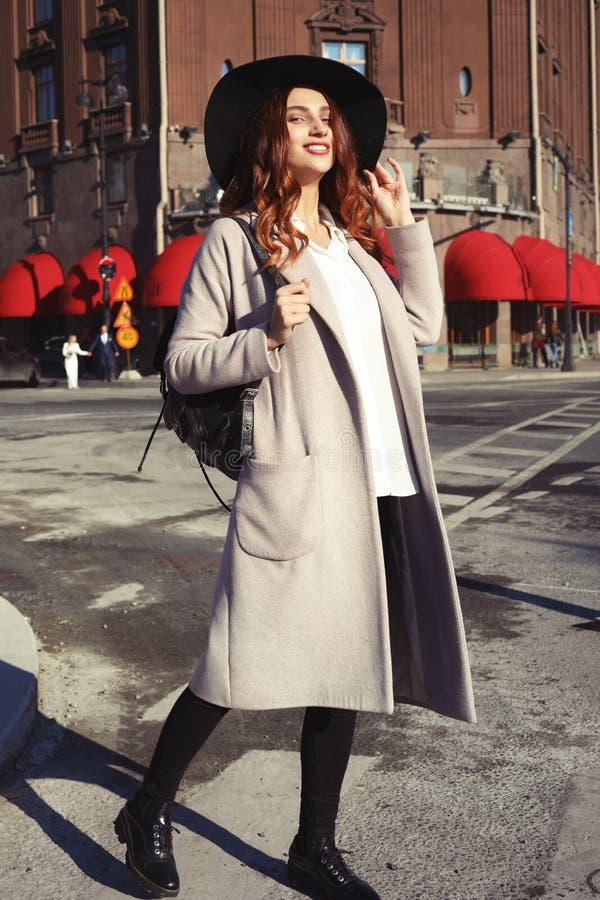 Ritratto di bella donna sorridente felice di Yong che porta cappello alla moda, cappotto Camminata di modello in via della città  fotografie stock