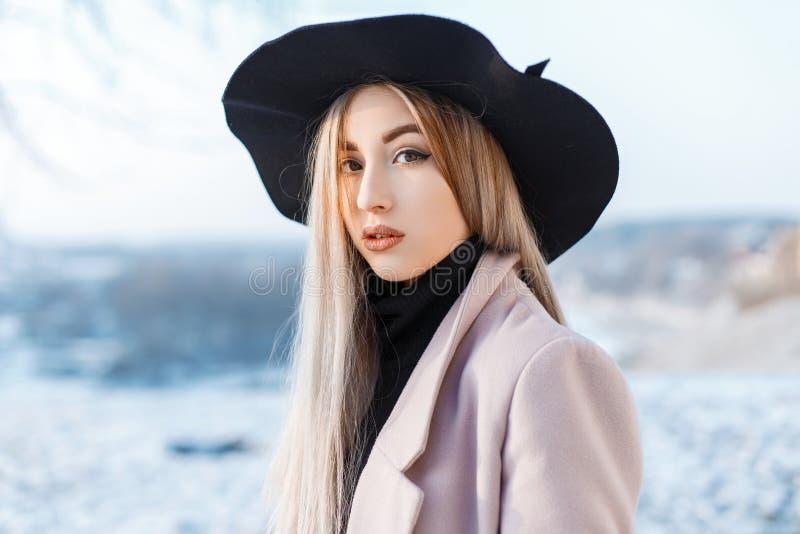 Ritratto di bella donna sveglia con trucco naturale con pelle pulita in un cappello elegante alla moda in un cappotto rosa fotografia stock