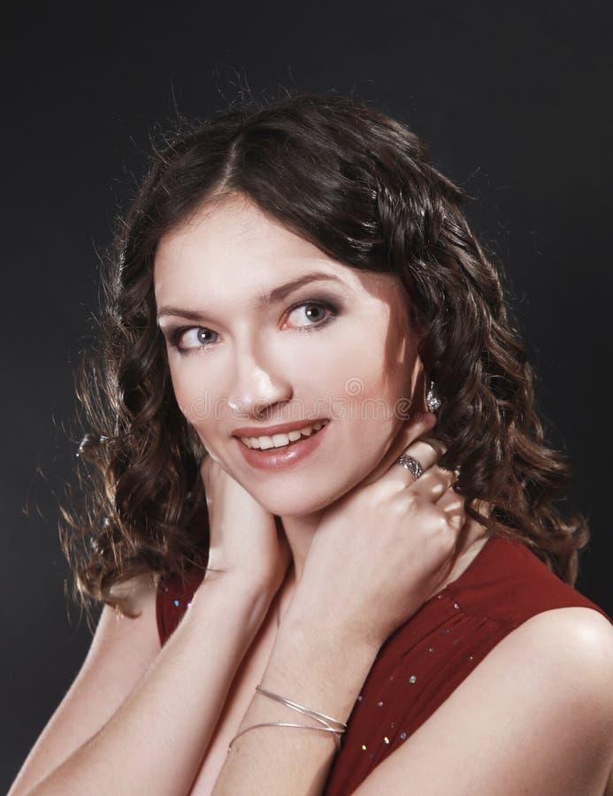 Ritratto di bella donna in vestito rosso che posa per la macchina fotografica fotografia stock