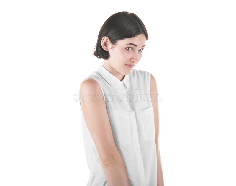 Ritratto di bella e ragazza timida, isolato su un fondo bianco La donna sola e sveglia in una blusa bianca alla moda immagine stock