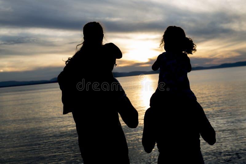 Ritratto di bella famiglia felice quattro insieme al tramonto immagine stock libera da diritti