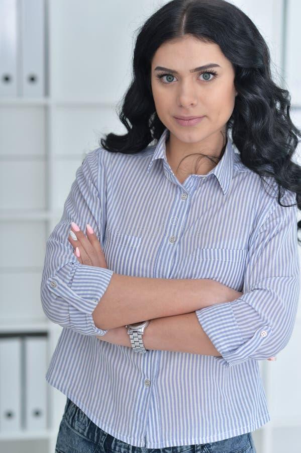 Ritratto di bella giovane condizione della donna di affari nell'ufficio immagini stock libere da diritti