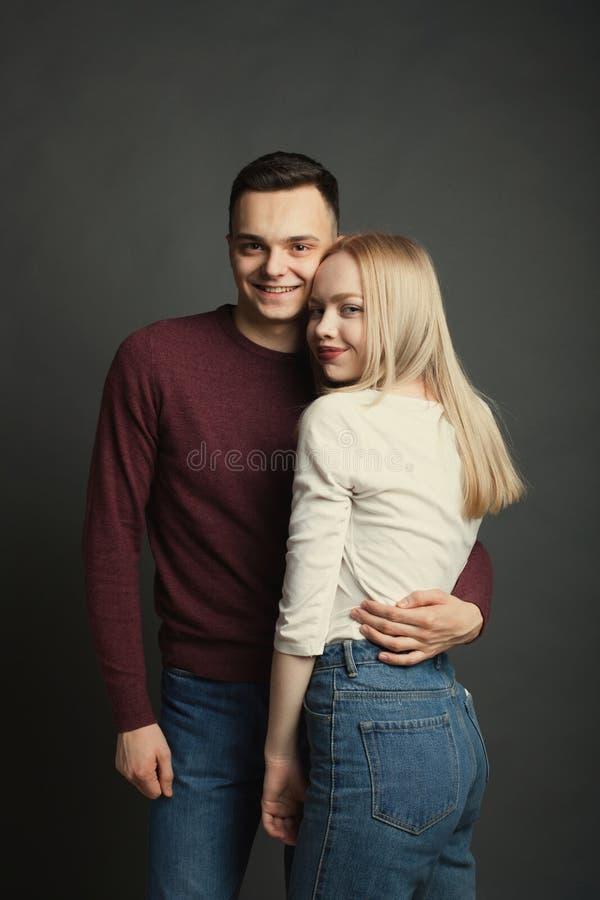 Ritratto di bella giovane coppia nell'amore che posa allo studio sopra fondo scuro fotografie stock