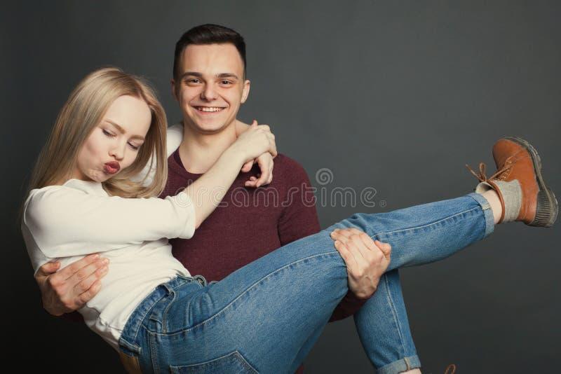 Ritratto di bella giovane coppia nell'amore che posa allo studio sopra fondo scuro Il tipo giudica il suo caro nelle suoi armi e  fotografia stock