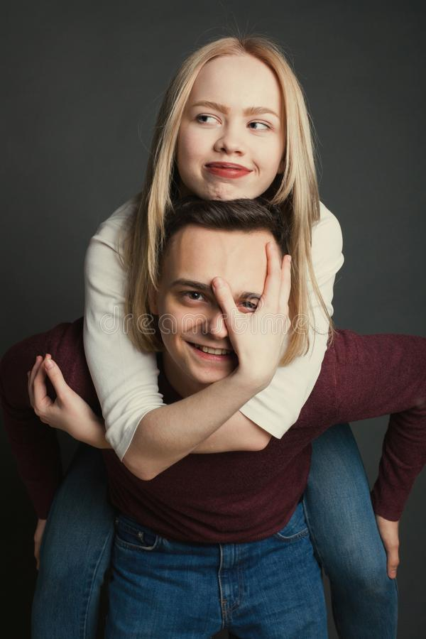 Ritratto di bella giovane coppia nell'amore che posa allo studio sopra fondo scuro Ragazza che si siede sulle spalle di un giovan fotografia stock