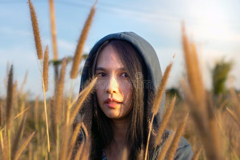 Ritratto di bella giovane donna asiatica che gode della natura sul prato dell'erba all'alba fotografia stock