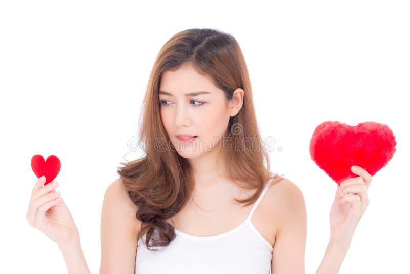 Ritratto di bella giovane donna asiatica che sorridono giudicando scelta rossa del cuscino di forma del cuore grande e di piccolo immagine stock