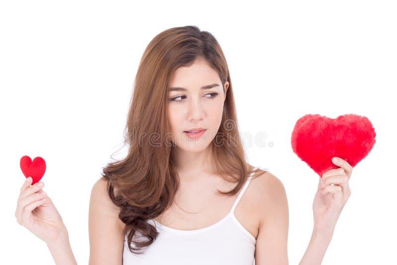 Ritratto di bella giovane donna asiatica che sorridono giudicando scelta rossa del cuscino di forma del cuore grande e di piccolo fotografie stock libere da diritti