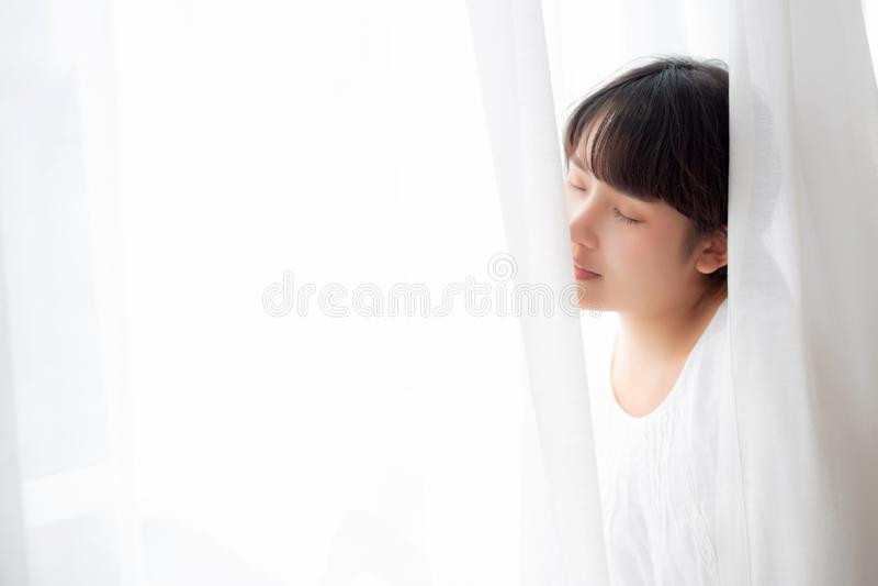 Ritratto di bella giovane donna asiatica che sta la finestra e sorriso mentre svegli con l'alba alla mattina fotografia stock libera da diritti