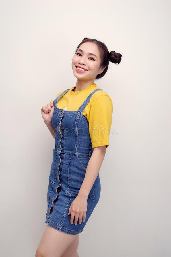 Ritratto di bella giovane donna asiatica con i panini dei capelli e di esame civettuolo la macchina fotografica su fondo bianco immagini stock