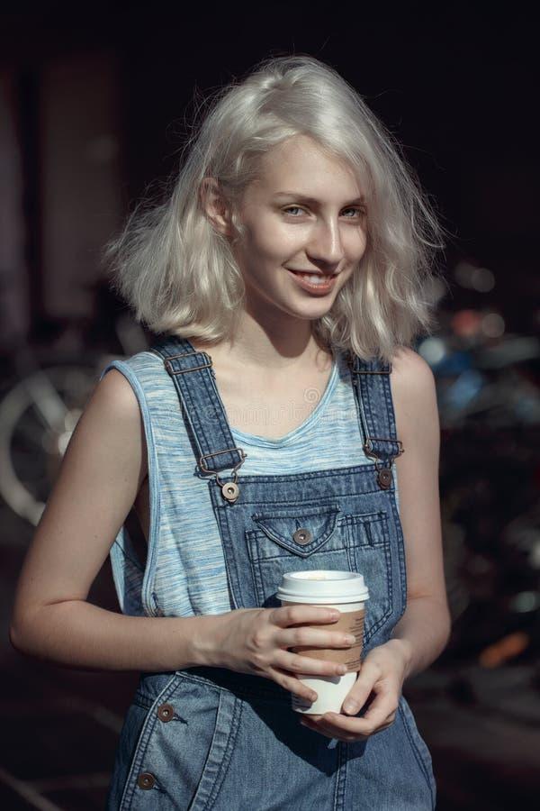 Ritratto di bella giovane donna bionda adolescente caucasica della ragazza del modello alternativo in maglietta blu, pagliaccetto immagini stock