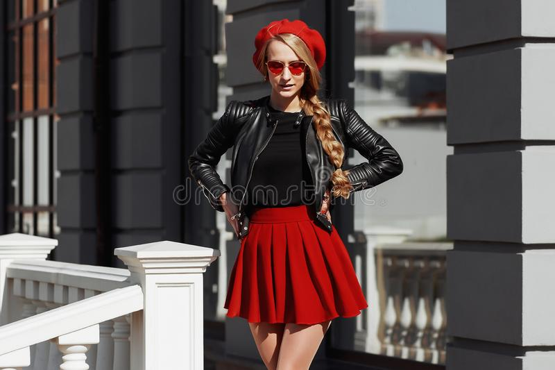 Ritratto di bella giovane donna bionda che indossa attrezzatura nera alla moda, lei che sorride sul fondo urbano fotografie stock