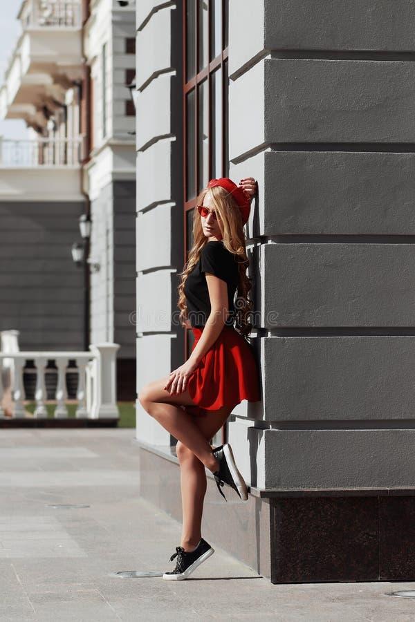 Ritratto di bella giovane donna bionda che indossa attrezzatura nera alla moda, lei che sorride sul fondo urbano immagini stock libere da diritti