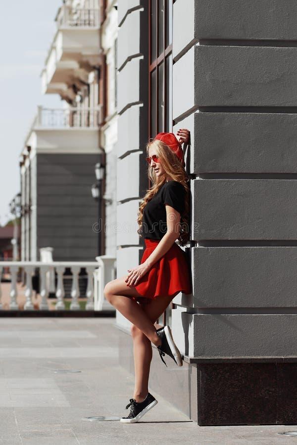 Ritratto di bella giovane donna bionda che indossa attrezzatura nera alla moda, lei che sorride sul fondo urbano immagine stock