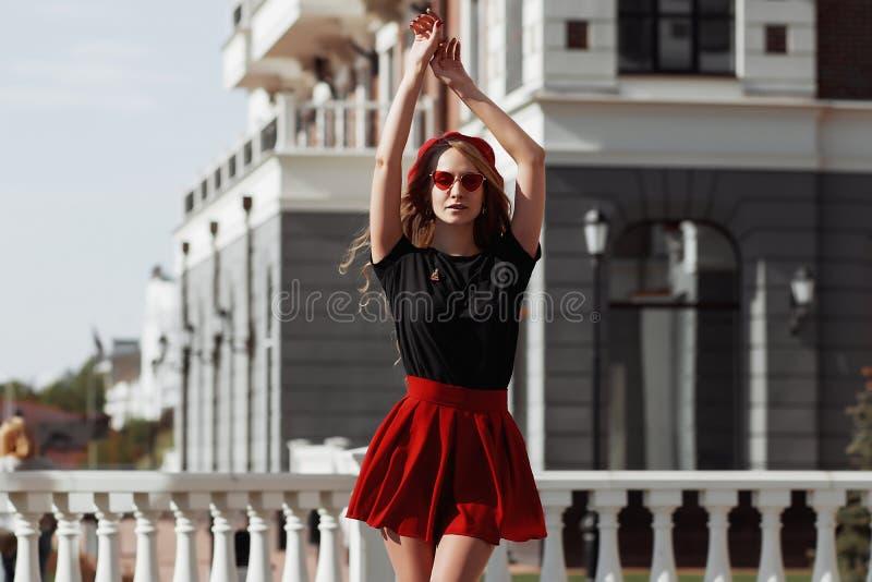 Ritratto di bella giovane donna bionda che indossa attrezzatura nera alla moda, lei che sorride sul fondo urbano fotografia stock