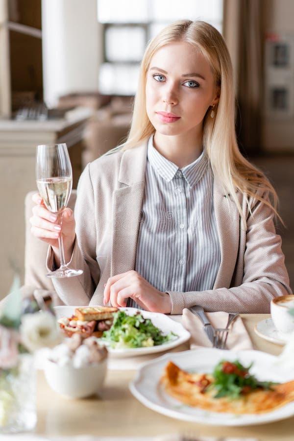 Ritratto di bella giovane donna bionda elegante nel caffè con un vetro di champagne fotografia stock