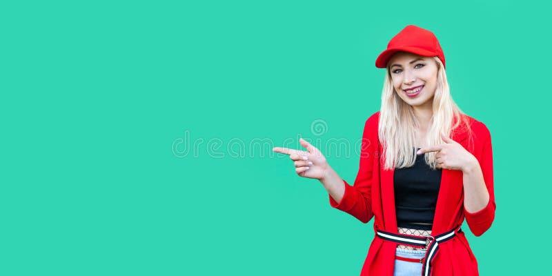 Ritratto di bella giovane donna bionda felice dei pantaloni a vita bassa in blusa e cappuccio rossi, stando, indicando al copyspa fotografia stock libera da diritti