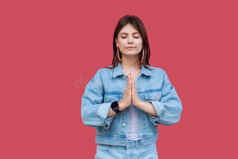 Ritratto di bella giovane donna castana calma con trucco nella condizione di stile casuale del denim con le mani della palma e ne immagini stock
