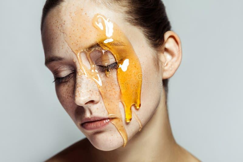 Ritratto di bella giovane donna castana con le lentiggini ed il miele sul fronte con gli occhi chiusi ed il fronte serio fotografia stock