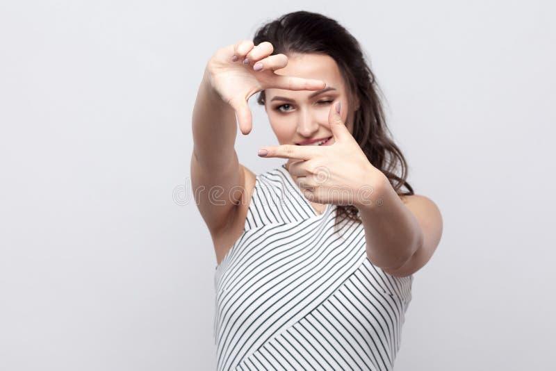 Ritratto di bella giovane donna castana con trucco e la condizione a strisce del vestito e l'esame della macchina fotografica con fotografia stock